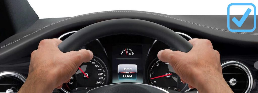 Persons hands are on car steering wheel.
